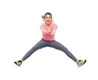 Mujer joven deportiva sonriente feliz que salta en aire Imagenes de archivo