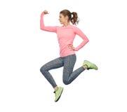 Mujer joven deportiva sonriente feliz que salta en aire Fotos de archivo libres de regalías