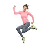 Mujer joven deportiva sonriente feliz que salta en aire Fotografía de archivo
