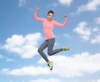Mujer joven deportiva sonriente feliz que salta en cielo Foto de archivo
