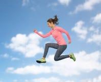 Mujer joven deportiva sonriente feliz que salta en cielo Fotos de archivo