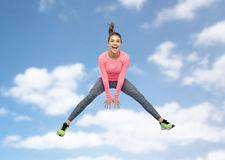 Mujer joven deportiva sonriente feliz que salta en cielo Fotografía de archivo libre de regalías