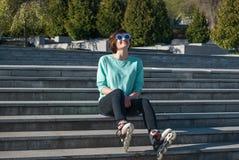 Mujer joven deportiva su encendido los pasos en el parque y expresivo Fotos de archivo