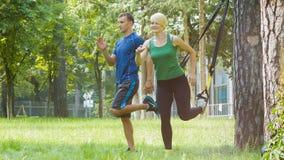Mujer joven deportiva y hombre o instructor que hacen el ejercicio gimnástico al aire libre