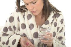 Mujer joven deprimida atractiva que siente mal y medicina que toma Hungover Foto de archivo