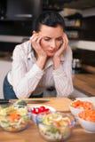 Mujer joven deprimida en cocina Imagen de archivo