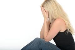Mujer joven deprimida infeliz trastornada que se sienta en el griterío del piso Foto de archivo