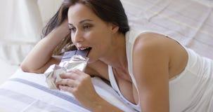 Mujer joven deprimida que come una barra de chocolate Imágenes de archivo libres de regalías