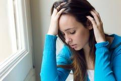 Mujer joven deprimida que se sienta en casa Foto de archivo
