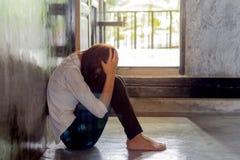 Mujer joven deprimida que se sienta en sitio vacío, imagenes de archivo