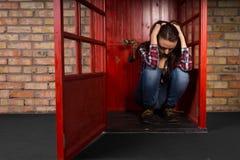 Mujer joven deprimida que se sienta en una cabina de teléfono Foto de archivo libre de regalías