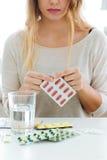Mujer joven deprimida que toma píldoras en casa Imagenes de archivo