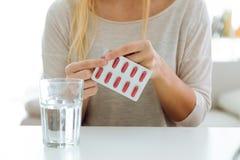 Mujer joven deprimida que toma píldoras en casa Fotos de archivo