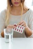 Mujer joven deprimida que toma píldoras en casa Fotografía de archivo libre de regalías