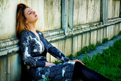 Mujer joven deprimida triste cerca de la pared sucia del grunge Foto de archivo