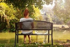 Mujer joven deprimida y triste que se sienta solamente en banco en el parque imagenes de archivo