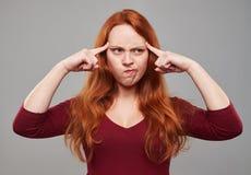 Mujer joven desconcertada con el pelo castaño que presiona su foreh Imágenes de archivo libres de regalías