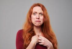 Mujer joven descontentada con el pelo castaño en el estudio Foto de archivo libre de regalías