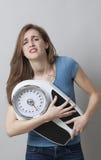 Mujer joven descontentada en dolor con la escala de la carga en manos Foto de archivo libre de regalías