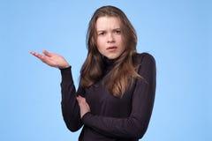 Mujer joven descontentada que frunce el ceño y que mira fijamente la cámara con mirada crítica foto de archivo