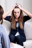 Mujer joven desesperada en la sesión de la psicoterapia Imágenes de archivo libres de regalías