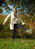 Mujer joven despreocupada que golpea el charco con el pie del agua en el parque Fotografía de archivo libre de regalías