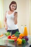 Mujer joven después de la receta en el teléfono móvil Fotos de archivo libres de regalías