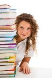 Mujer joven detrás de la pila de libros aislados en blanco Fotos de archivo