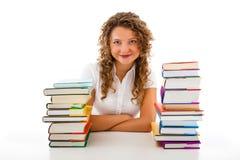 Mujer joven detrás de la pila de libros aislados en blanco Fotografía de archivo libre de regalías