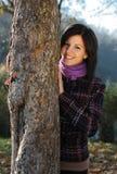 Mujer joven detrás de un árbol Fotografía de archivo