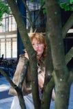 Mujer joven detrás de un árbol Fotos de archivo libres de regalías
