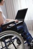 Mujer joven discapacitada que usa el ordenador portátil fotos de archivo