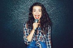 Mujer joven divertida con el micrófono que canta algo Imagenes de archivo