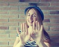 Mujer joven divertida con los apoyos en sus dientes en backgro de la pared de ladrillo Foto de archivo libre de regalías