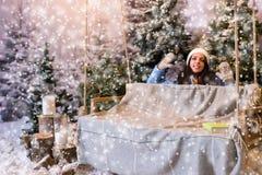 Mujer joven divertida en abajo chaqueta azul detrás de un oscilación en una nieve-c Fotografía de archivo libre de regalías
