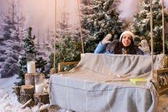 Mujer joven divertida en abajo chaqueta azul detrás de un oscilación en una nieve-c Fotos de archivo libres de regalías