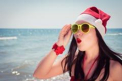 Mujer joven divertida en el sombrero y las gafas de sol de Santa Claus Fotografía de archivo libre de regalías