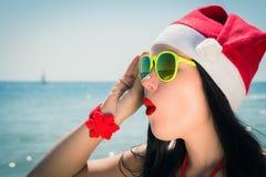 Mujer joven divertida en el sombrero y las gafas de sol de Santa Claus Imagen de archivo