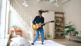Mujer joven divertida en los auriculares que saltan en cama con la guitarra eléctrica en dormitorio en casa dentro Imagen de archivo
