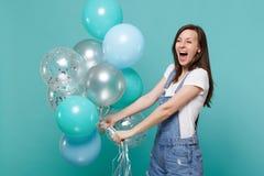 Mujer joven divertida feliz extática en ropa del dril de algodón que grita, celebrando y sosteniendo los balones de aire colorido imagen de archivo