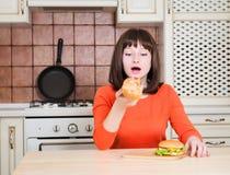 Mujer joven divertida hermosa que come la pizza y la hamburguesa del pan francés Fotos de archivo