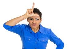 Mujer joven divertida que exhibe la muestra del perdedor en su frente Fotos de archivo