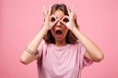 Mujer joven divertida que gesticula con los fingeres y que mira la cámara Imagen de archivo