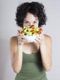 Mujer joven divertida que mira detrás de una ensalada vegetal Foto de archivo