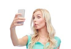 Mujer joven divertida que toma el selfie con smartphone Foto de archivo