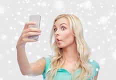 Mujer joven divertida que toma el selfie con smartphone Foto de archivo libre de regalías