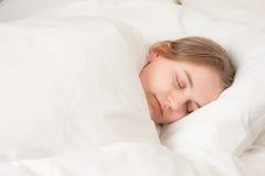 Mujer joven dormida en cama Imágenes de archivo libres de regalías