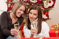 Mujer joven dos con champán y el árbol de navidad Imagen de archivo