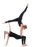 Mujer joven dos en ejercicio acrobático de la demostración negra Imagenes de archivo