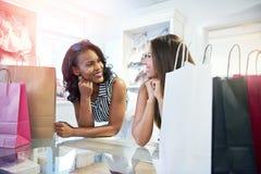 Mujer joven dos en un boutique de la ropa imagen de archivo